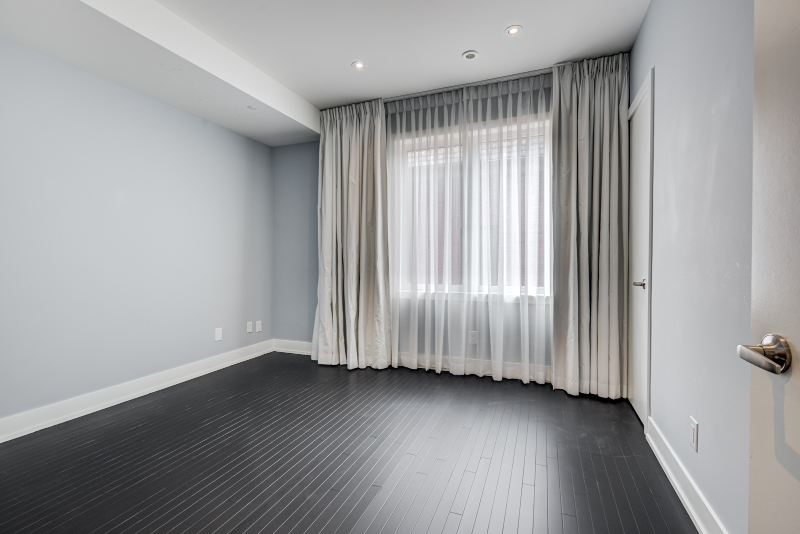 empty bedroom of 12A Cecil with black floors and blue walls