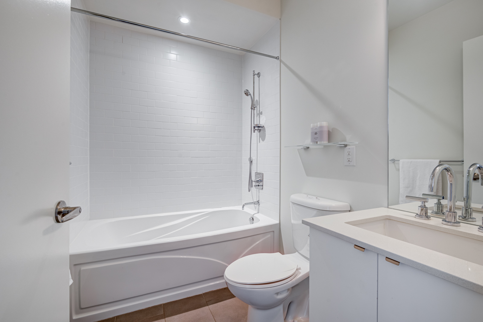 Bathroom with white tiles, tub, shelves and vanity