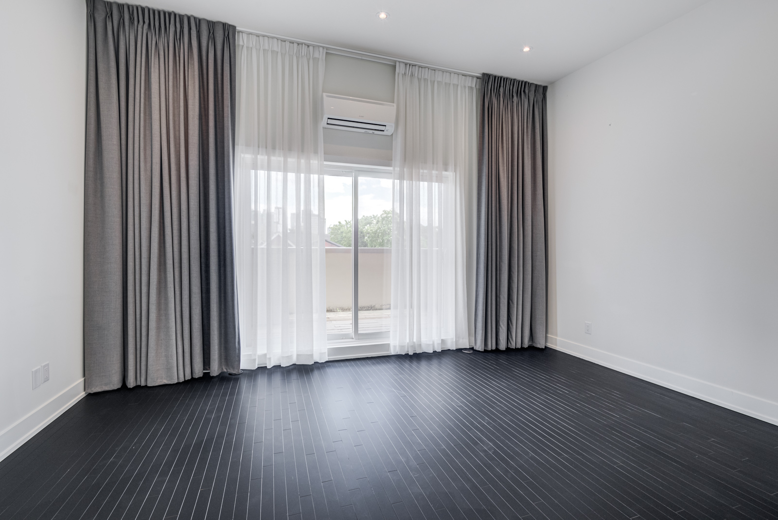 Empty master bedroom with black floors and white and gray curtains