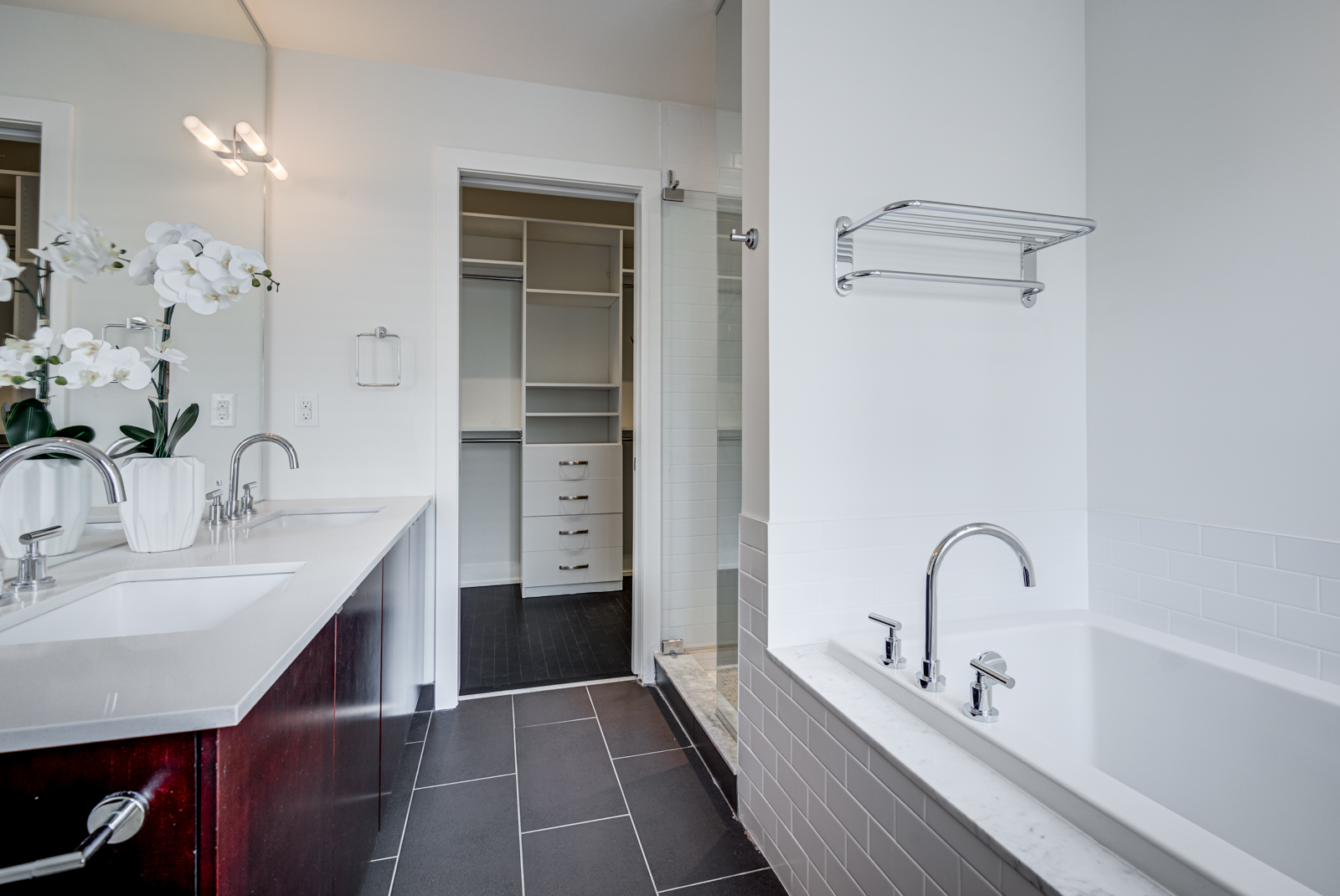 master bath with his and her sinks, soaker tub and black floor tiles.