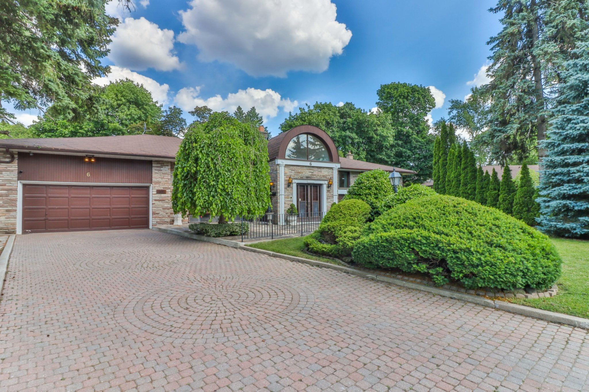 Large bungalow with 6-car driveway and huge front yard with trees.