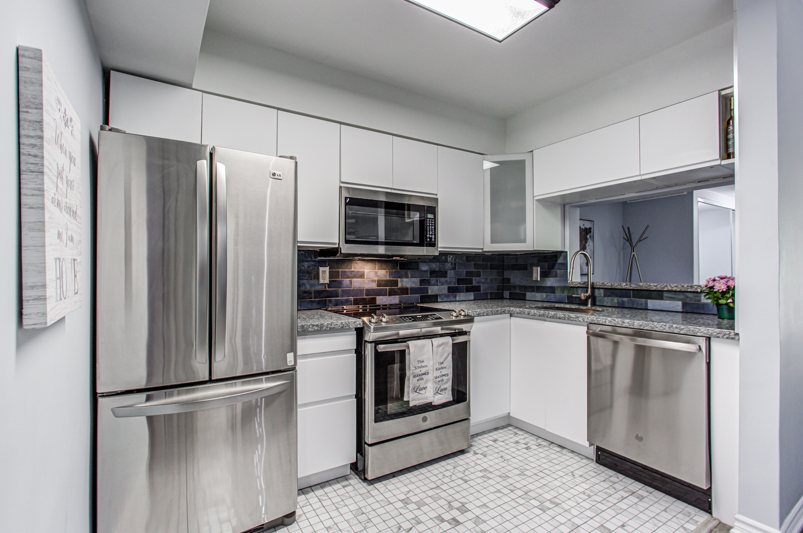 5 Everson Dr kitchen with gray cabinets, dark blue brick back-splash, and marble floor tiles.