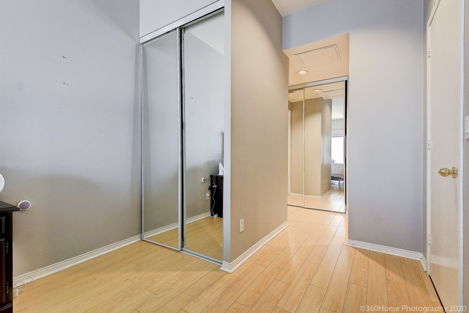 Light brown laminate floors and closet with mirror doors.