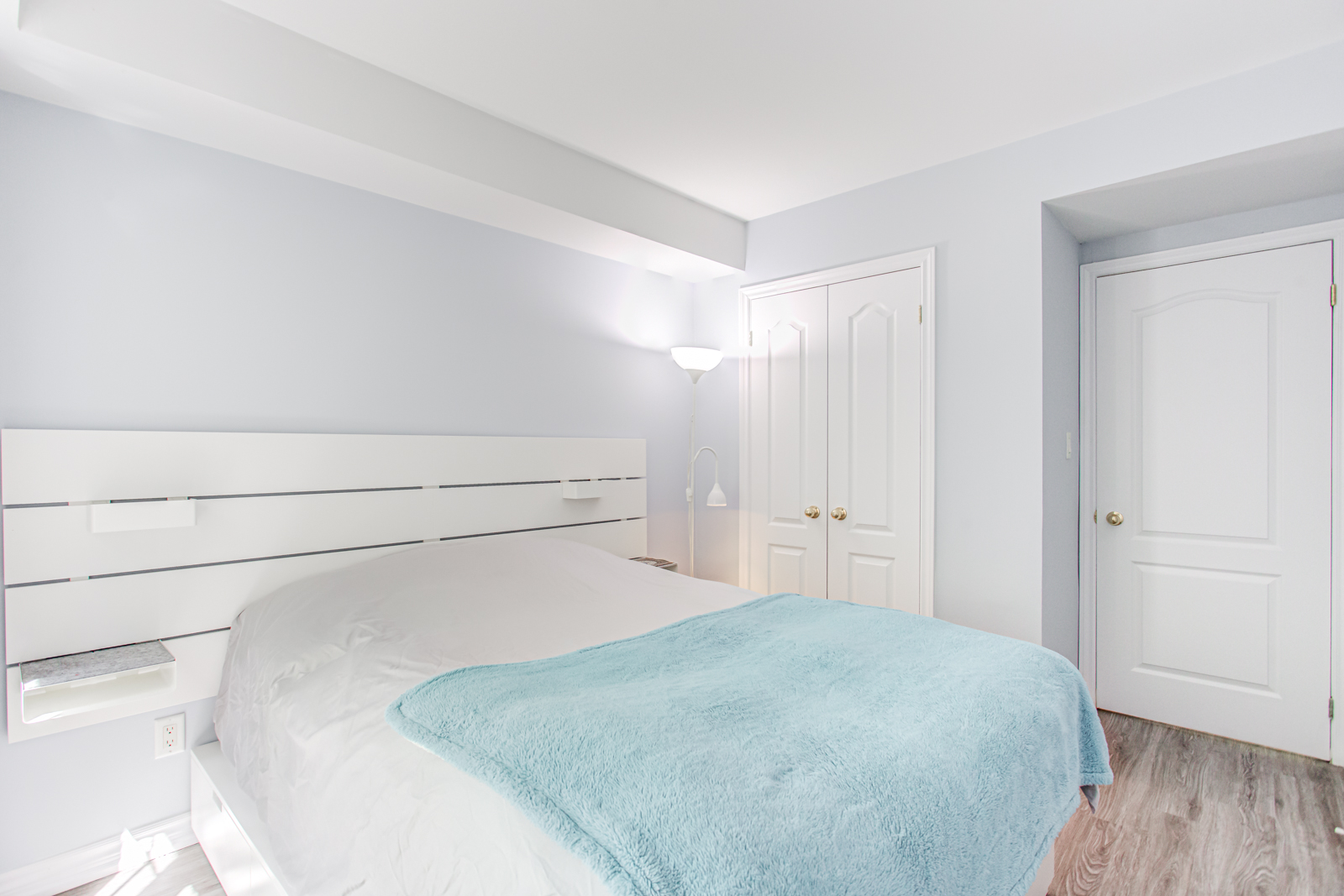 Alternate angle of master bedroom showing mostly white and gray color scheme.