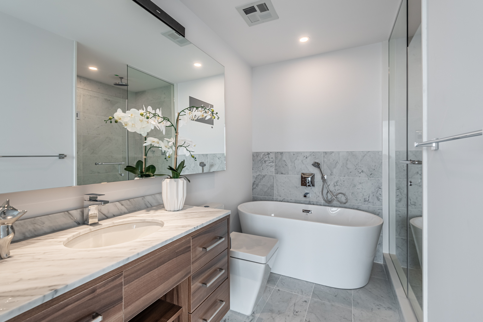 Freestanding soaking tub, large mirror and sink with vase.