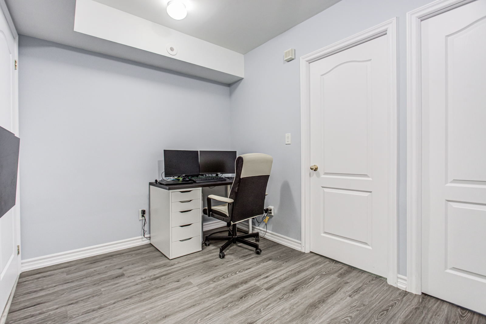 Home office with desk, chair with wheels, 2 computer monitors, and gray filing cabinet.