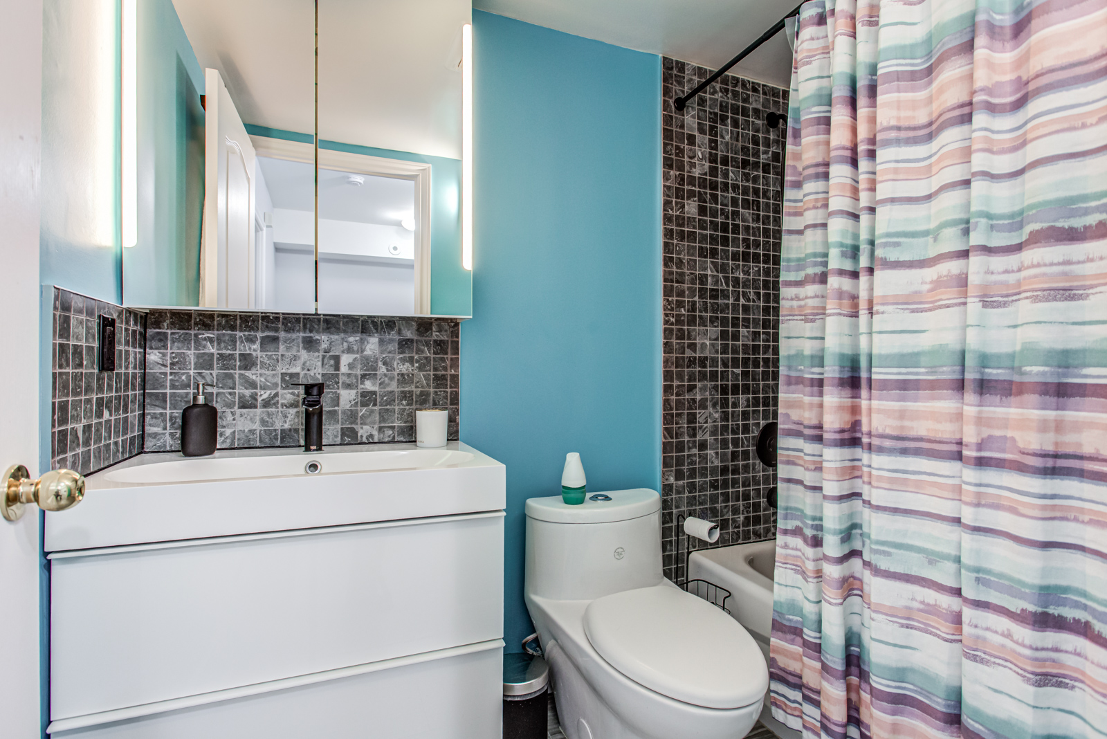 Newly-renovated bathroom with bright blue walls, small black tiles, colourful curtains and black faucet.