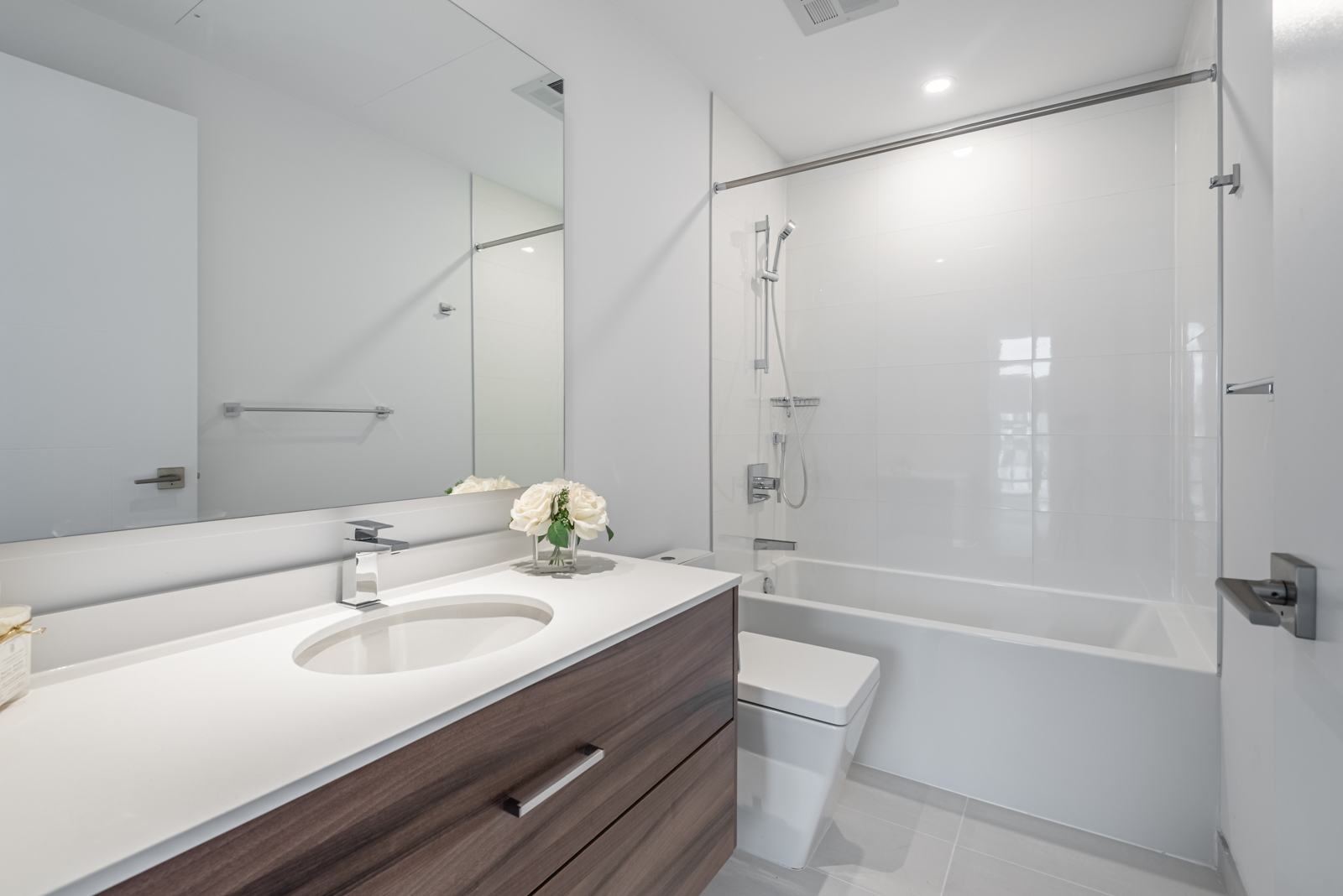 Bathroom with glistening white tiles, gray walls, soaker tub and large vanity.