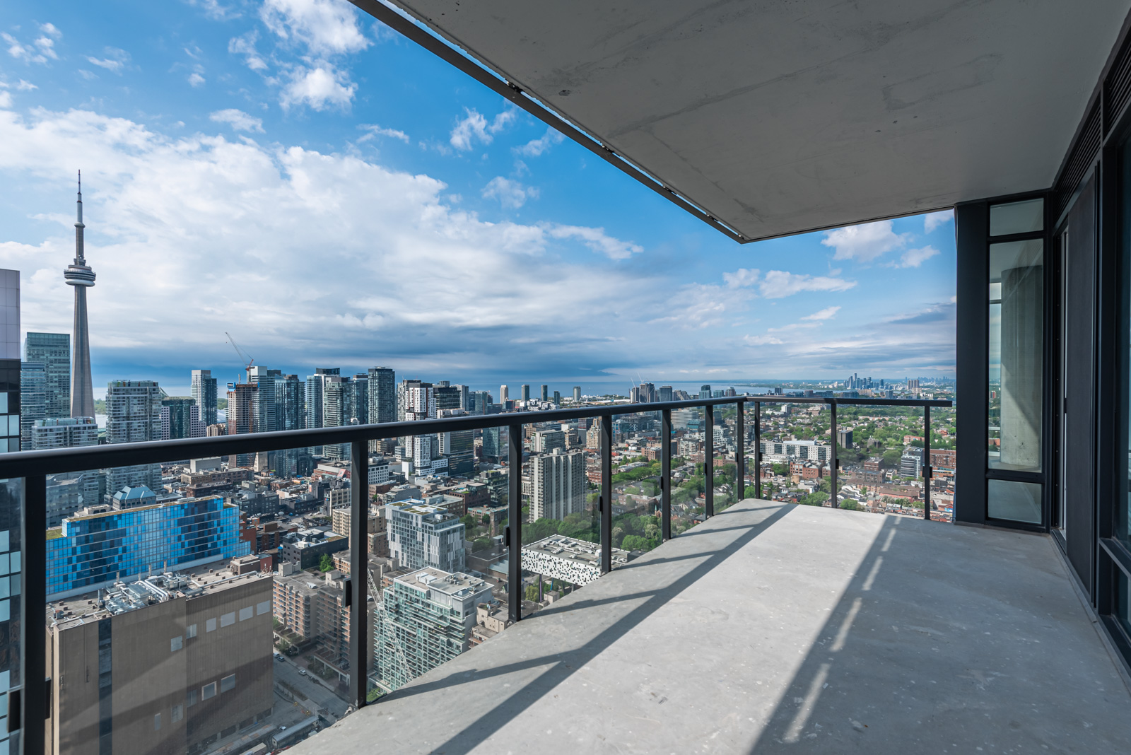 Balcony with clear glass panels showing CN Tower and Toronto.