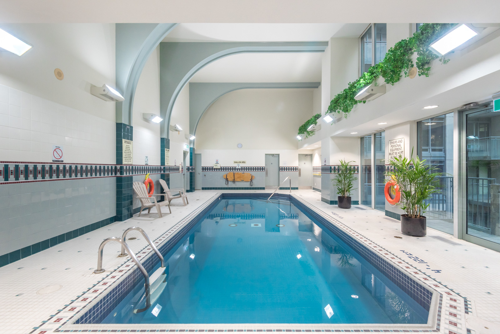 Indoor swimming pool with clear blue water and potted plants at The Metropole.