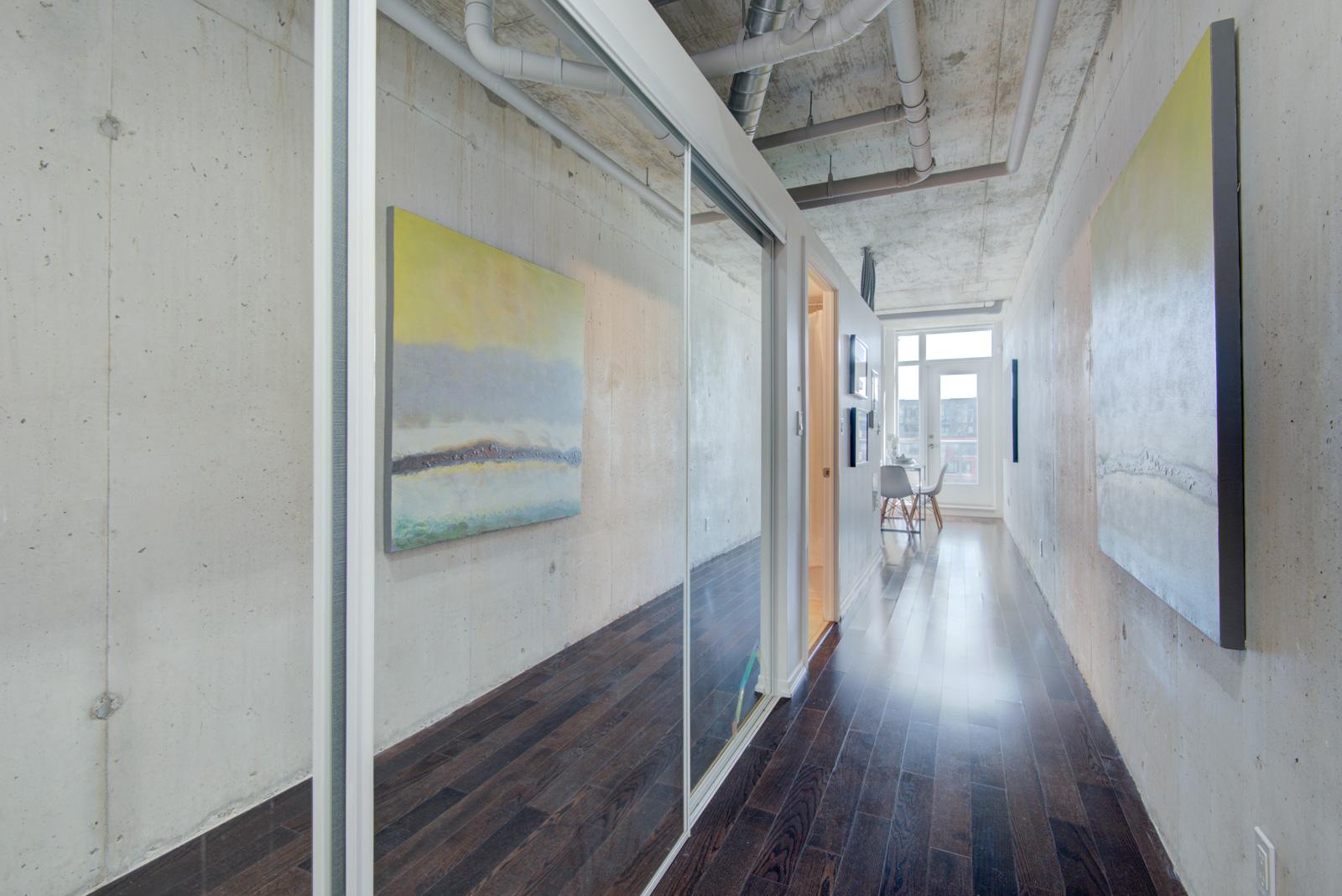 Condo hallway with mirror-door closet and exposed walls.