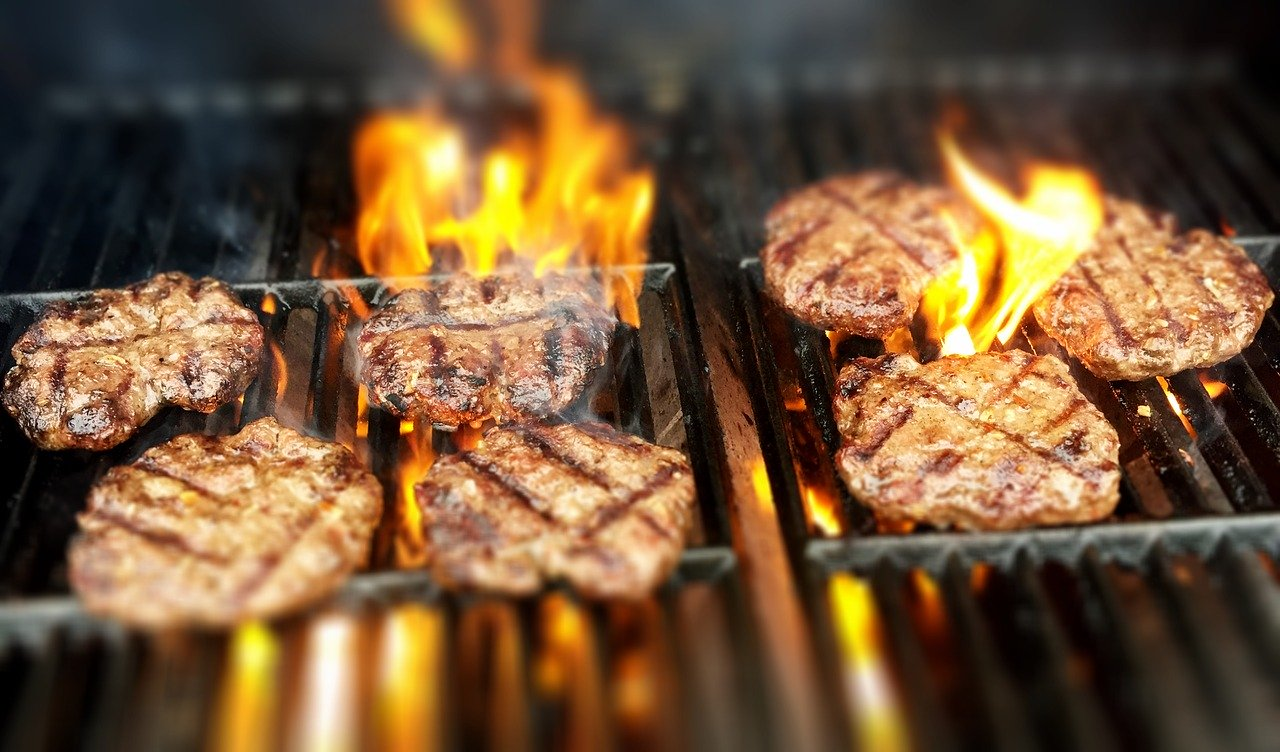 Close up of grill with 7 burger patties and flame.