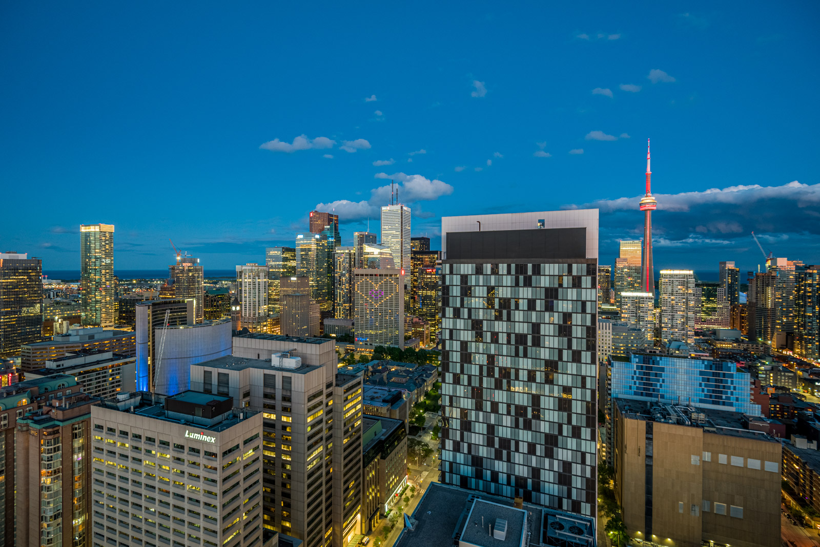Bright lights of Toronto and CN Tower at night seen from balcony of 488 University Ave.