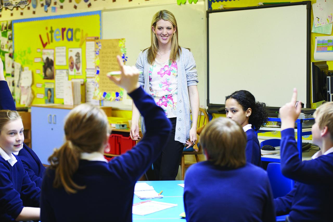 Elementary school kids in blue uniform raising hand for female teacher.