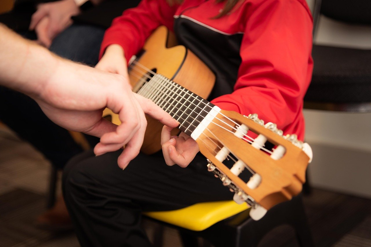 Close up of kid in red jacket learning to play guitar.