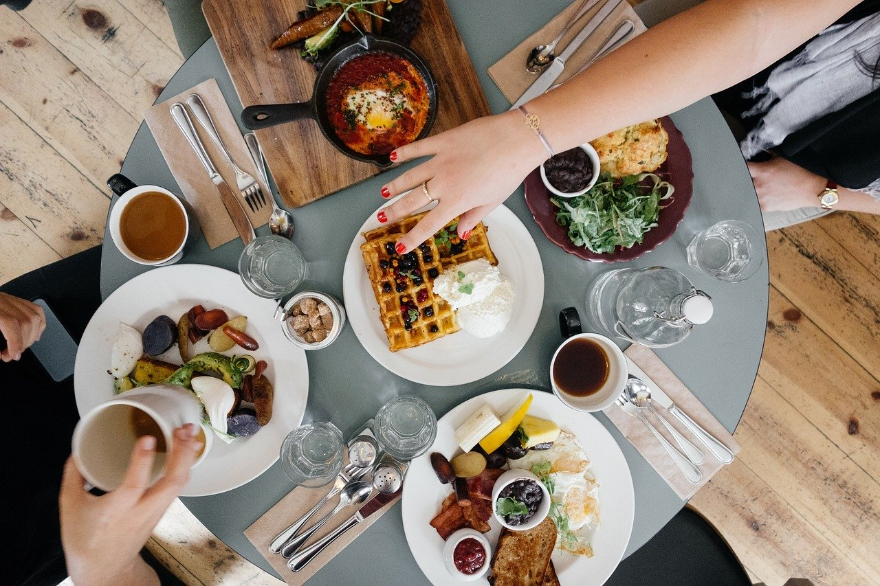 Top down view of breakfast table loaded with food.