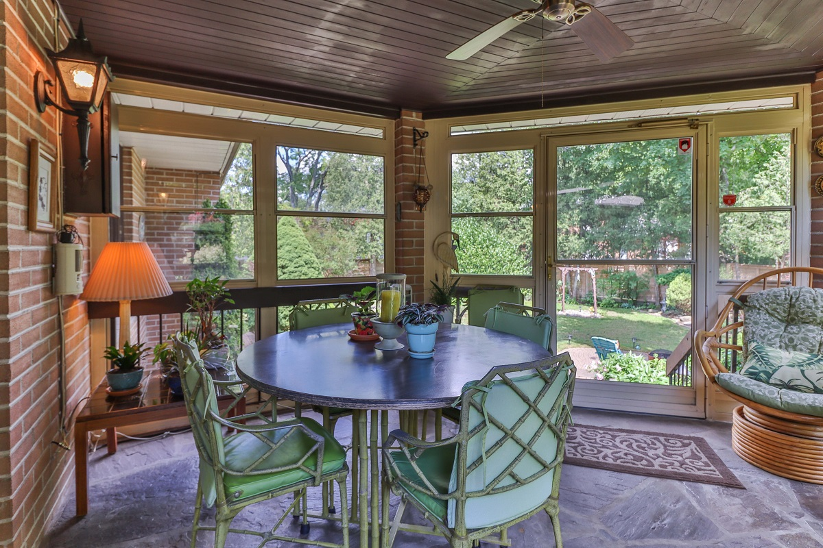 Enclosed patio with small table, few chairs, furniture and view of 6 Parmbelle Cres backyard.