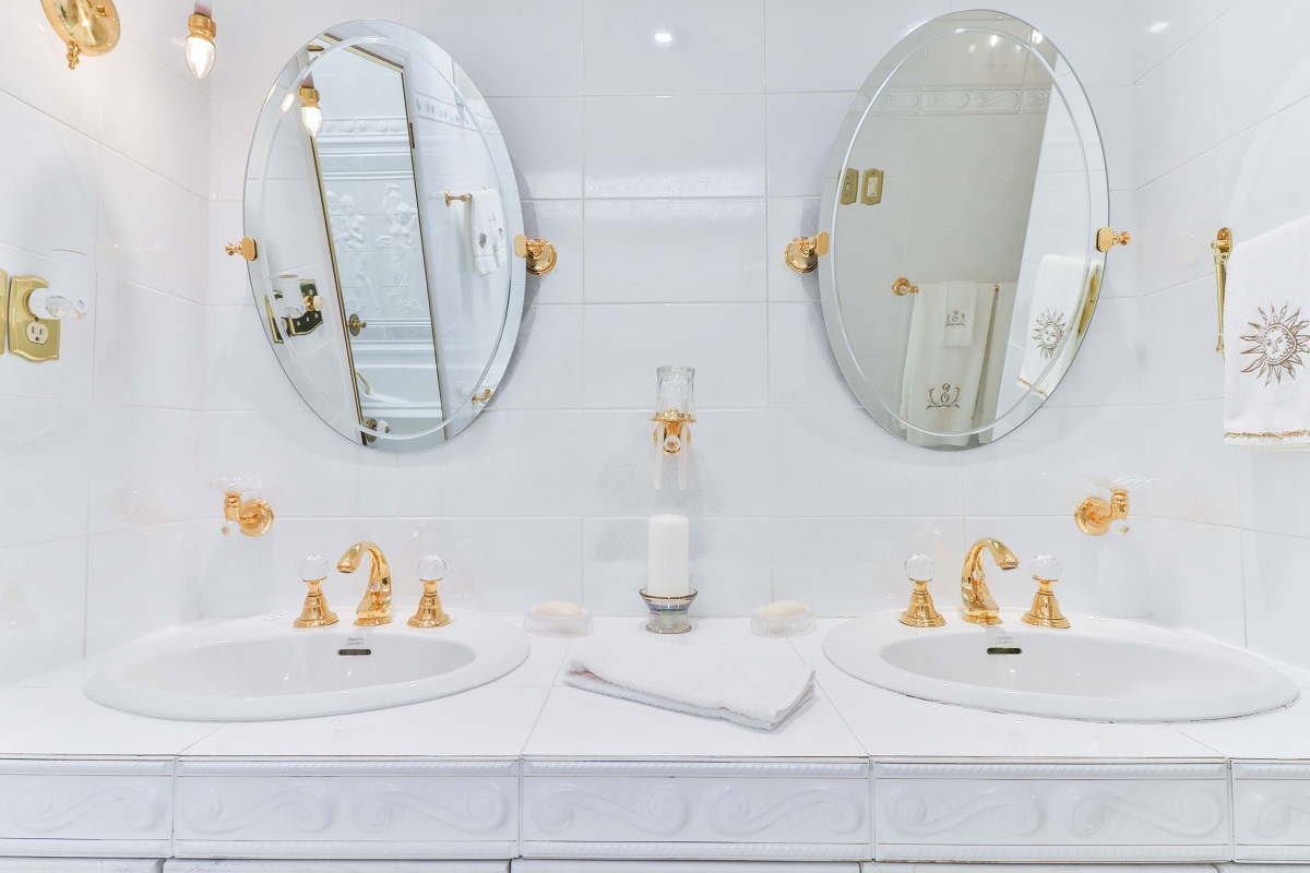 White bathroom with dual mirrors, sinks, and gold trims.