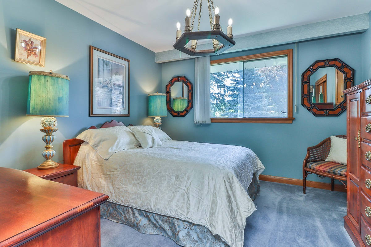 Bedroom with soft blue walls and broadloom carpet.
