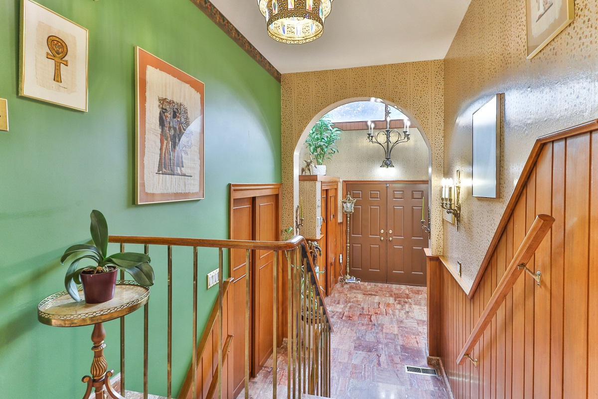 View of 6 Parmbelle Cres entrance, with double doors, 2 chandeliers and green walls.