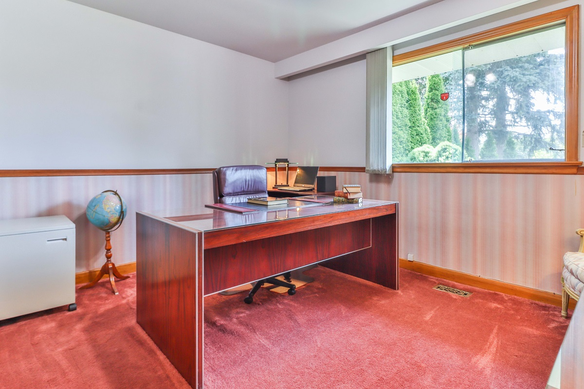 Office with large desk, window and red carpet.