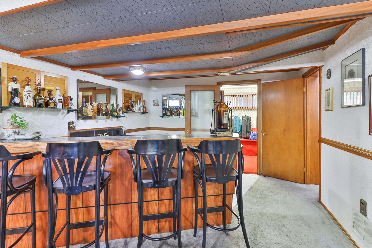 6 Parmbelle Cres basement wet bar with black chairs and alcohol on shelves.