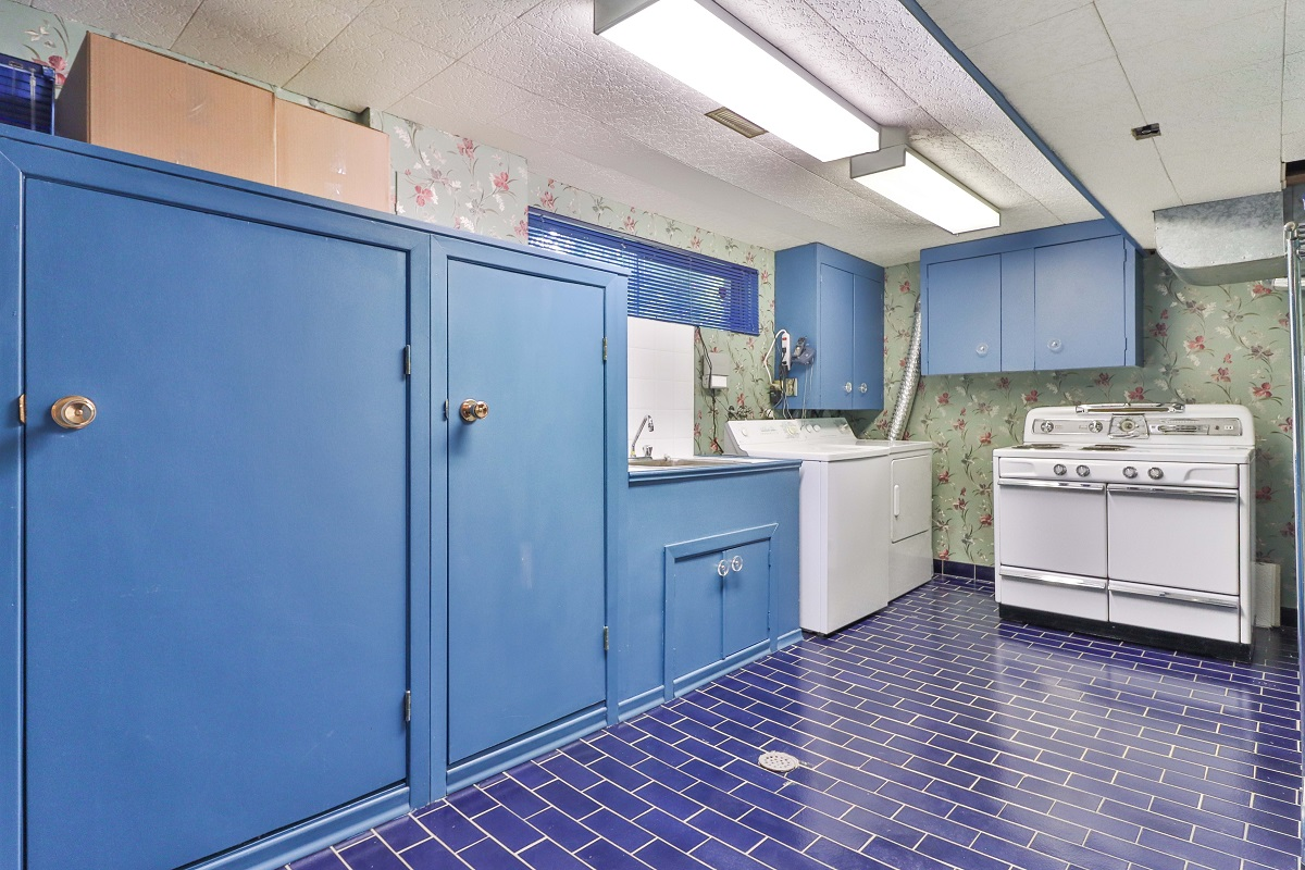 Chic laundry room with dark blue ceramic tiles and light blue cabinets.
