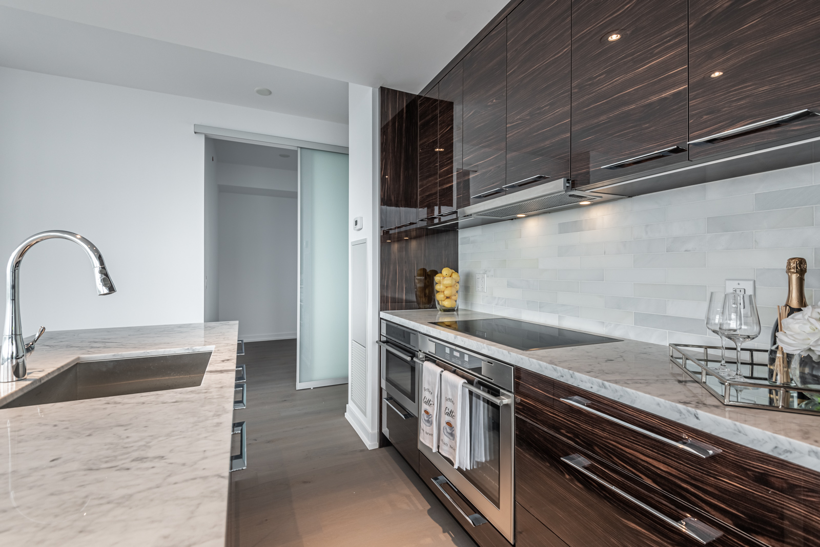 Glossy dark brown cabinets and white marble counter.