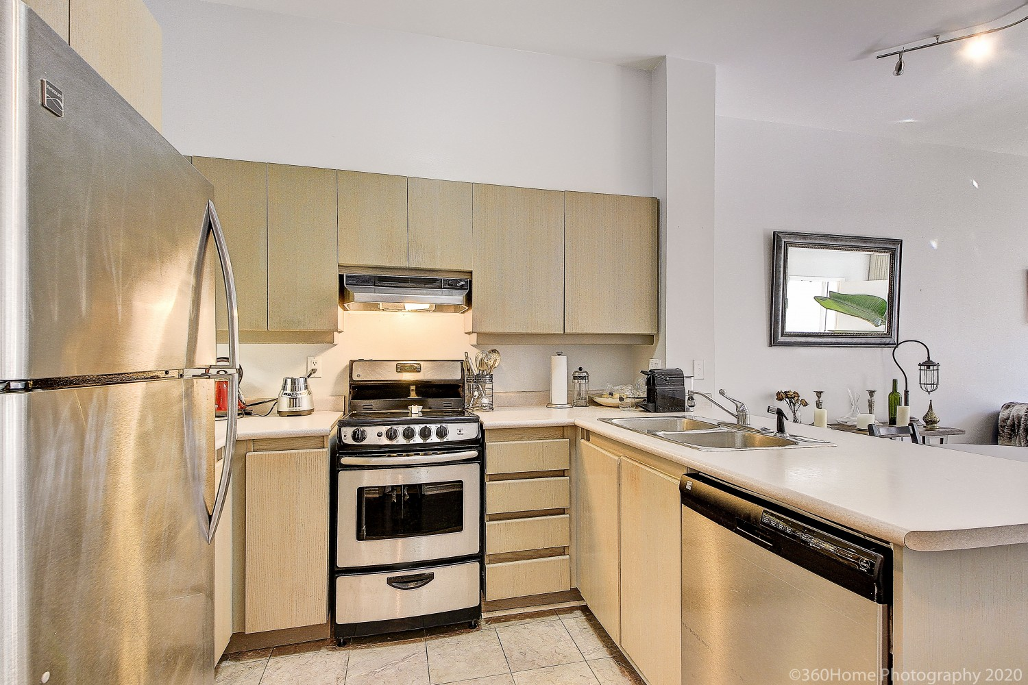 Somewhat old condo kitchen with beige cabinets, marble tiles and stainless-steel stove and fridge.