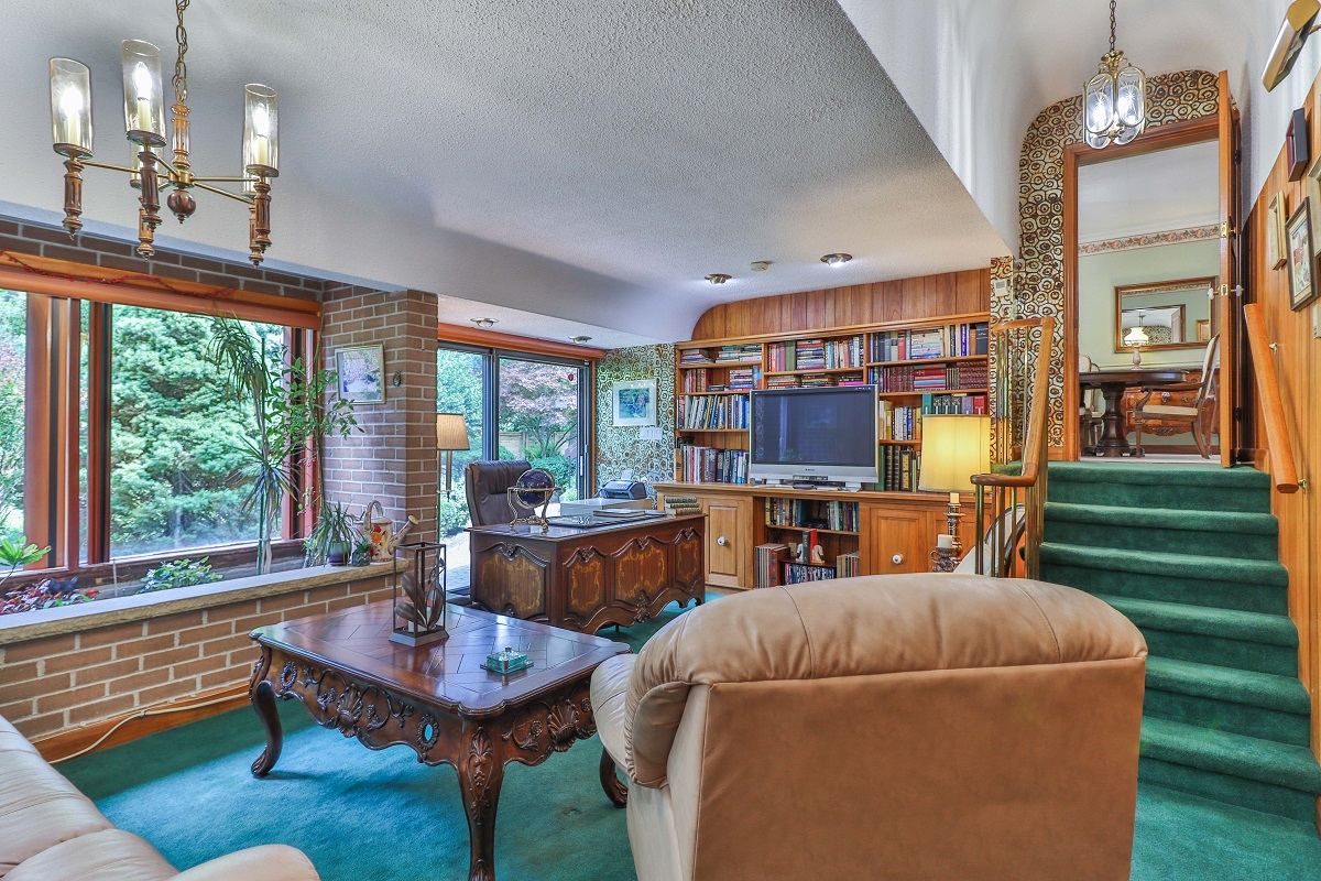 Bungalow library with wood paneling, chandeliers and green broadloom carpet.