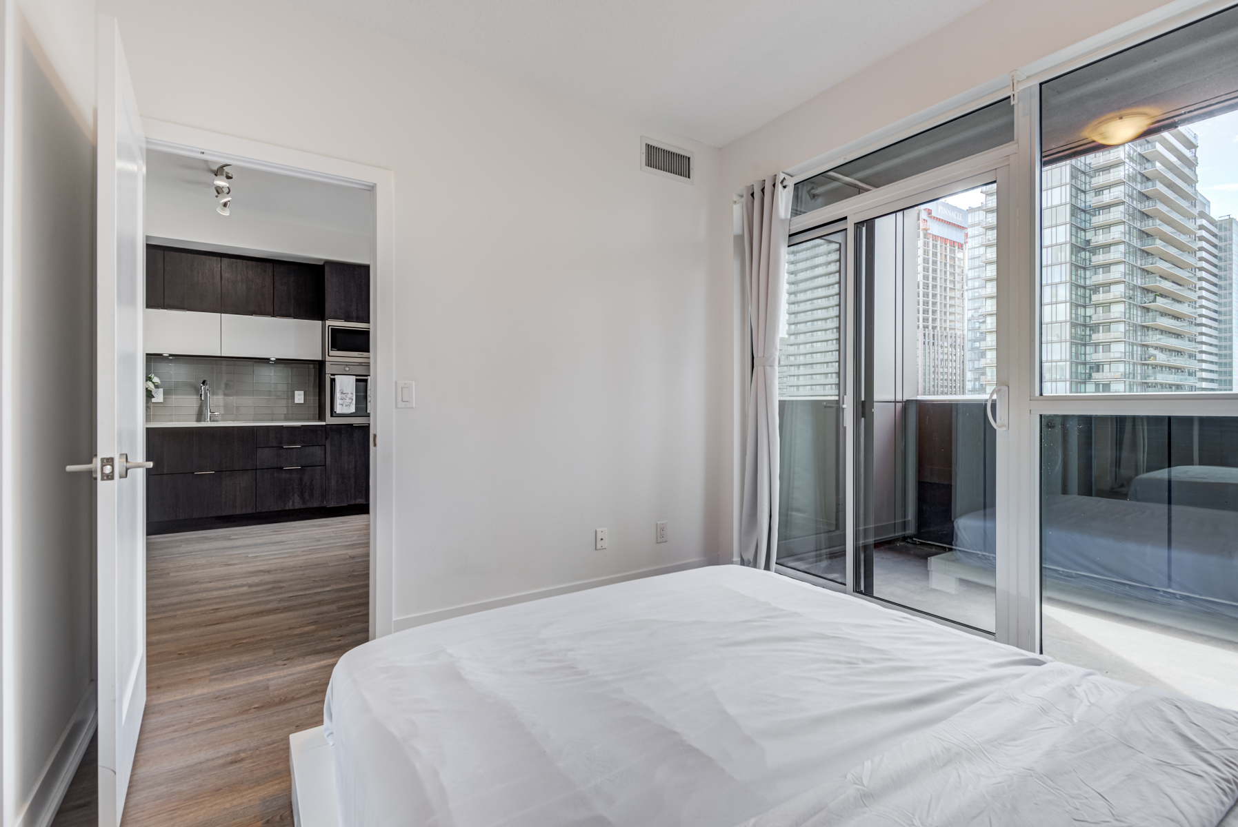 Condo bedroom with walk-out balcony showing Toronto in background.