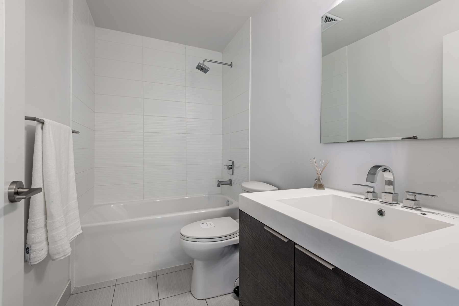 Bathroom with gray walls, white quartz counter and large vanity.