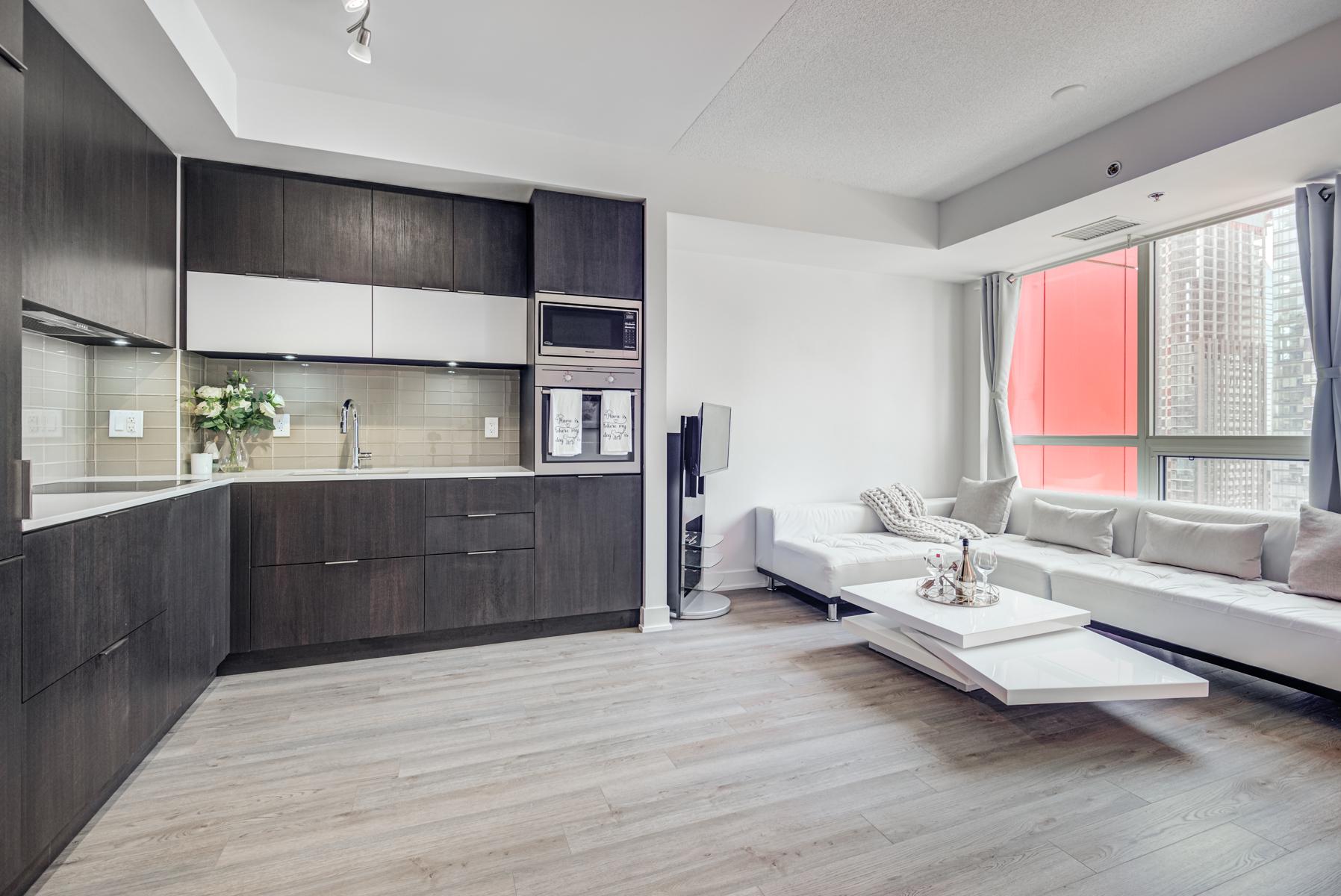 Sleek and elegant condo kitchen with dark cabinets.