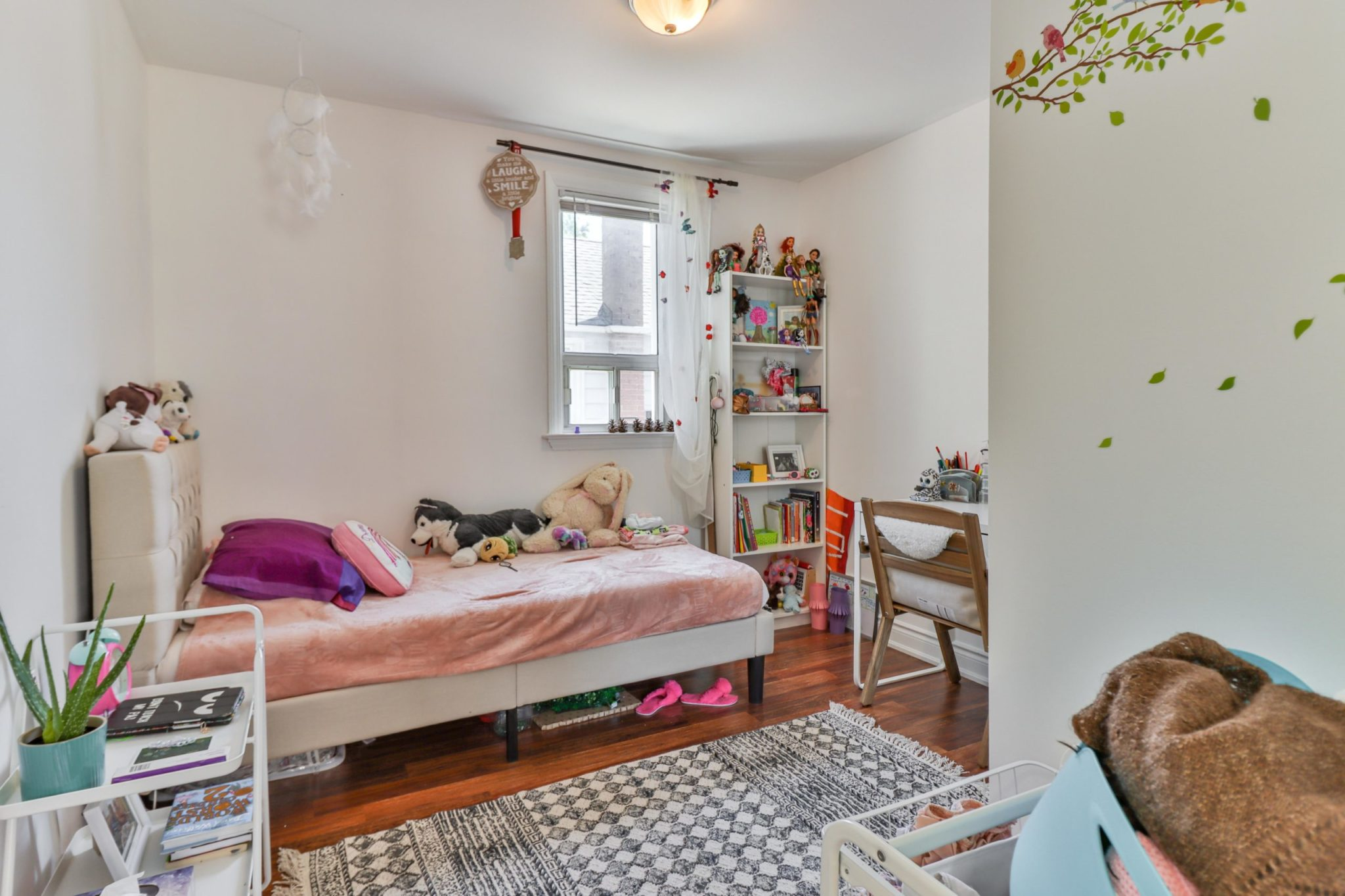 Girl's bedroom with pink walls, bookcase with dolls and stuffed animals on bed.
