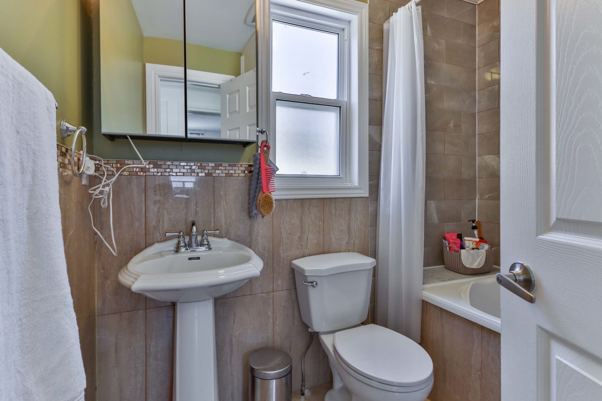 Newly renovated bathroom with beige-brown tiles, white sink, toilet and soaker tub.
