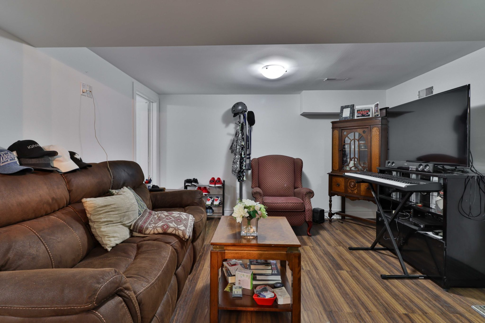 Large basement living room with big couch, TV, armchair, keyboard and other furniture.