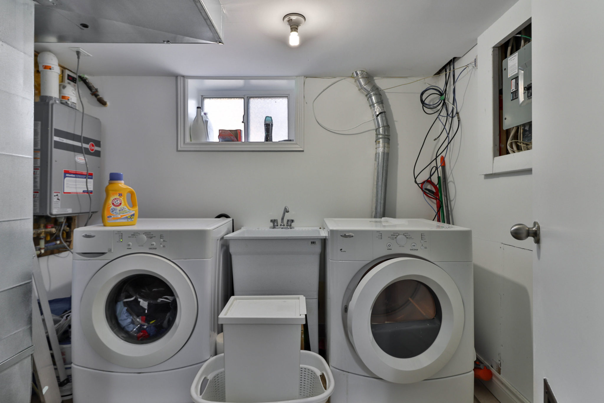 Laundry room with white front loading washer and dryer by Whirlpool.