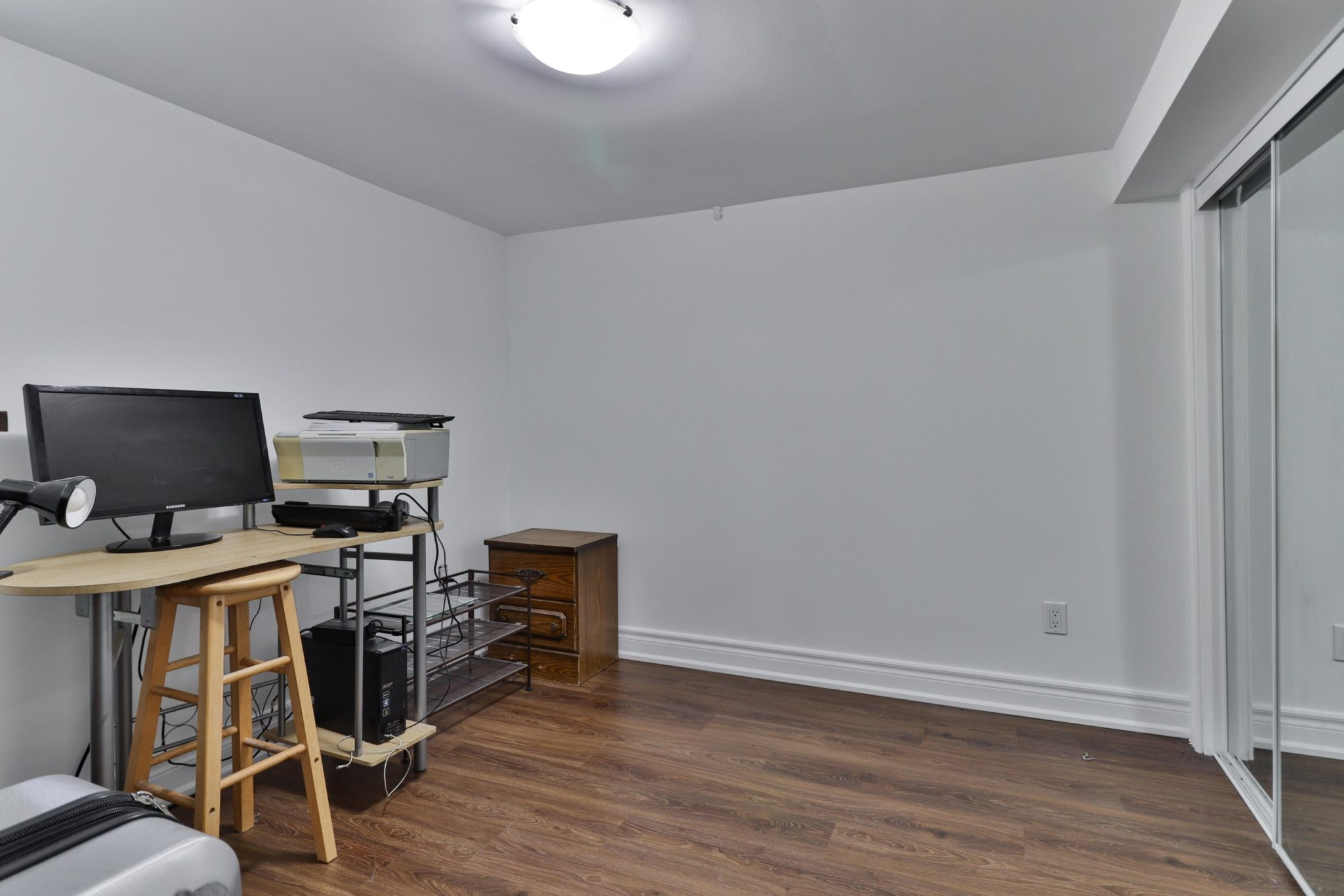 Basement bedroom being used as home office with computer, desk and chair.