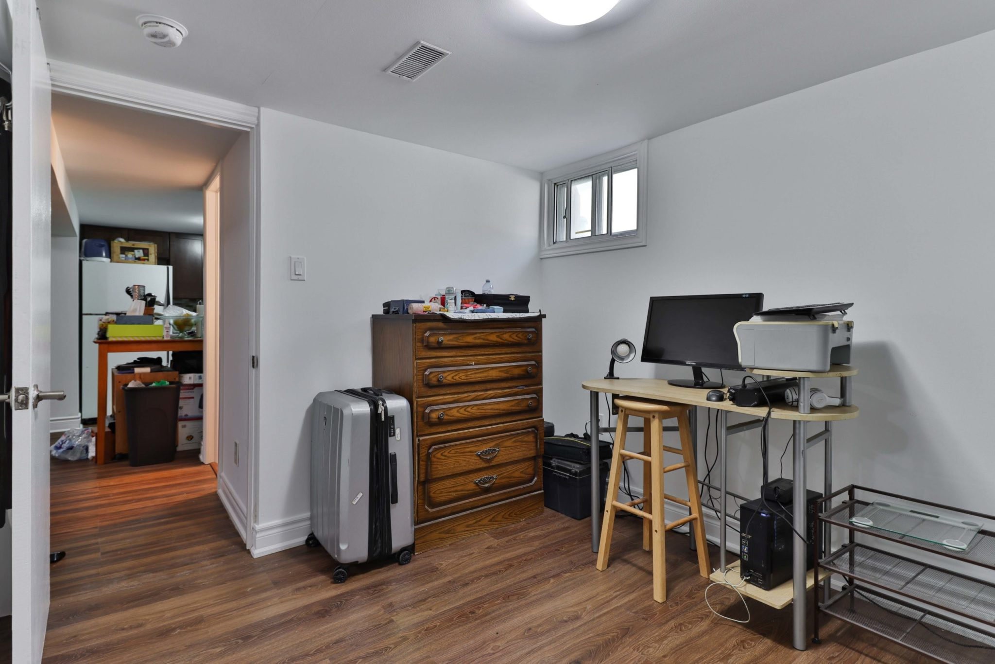 Basement office with computer, desk, large dresser, luggage and laminate floors.