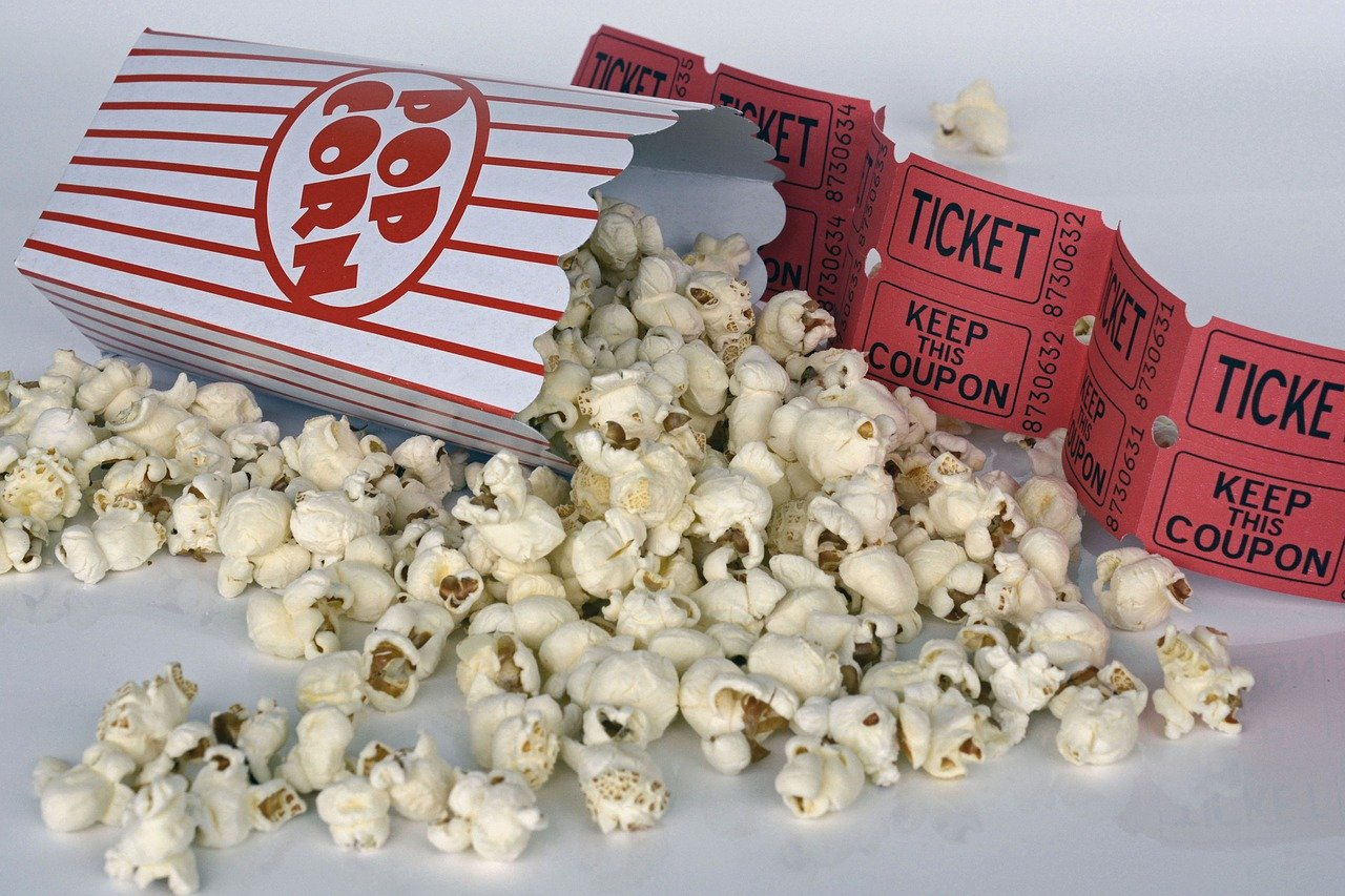 Spilled popcorn and red movie tickets.