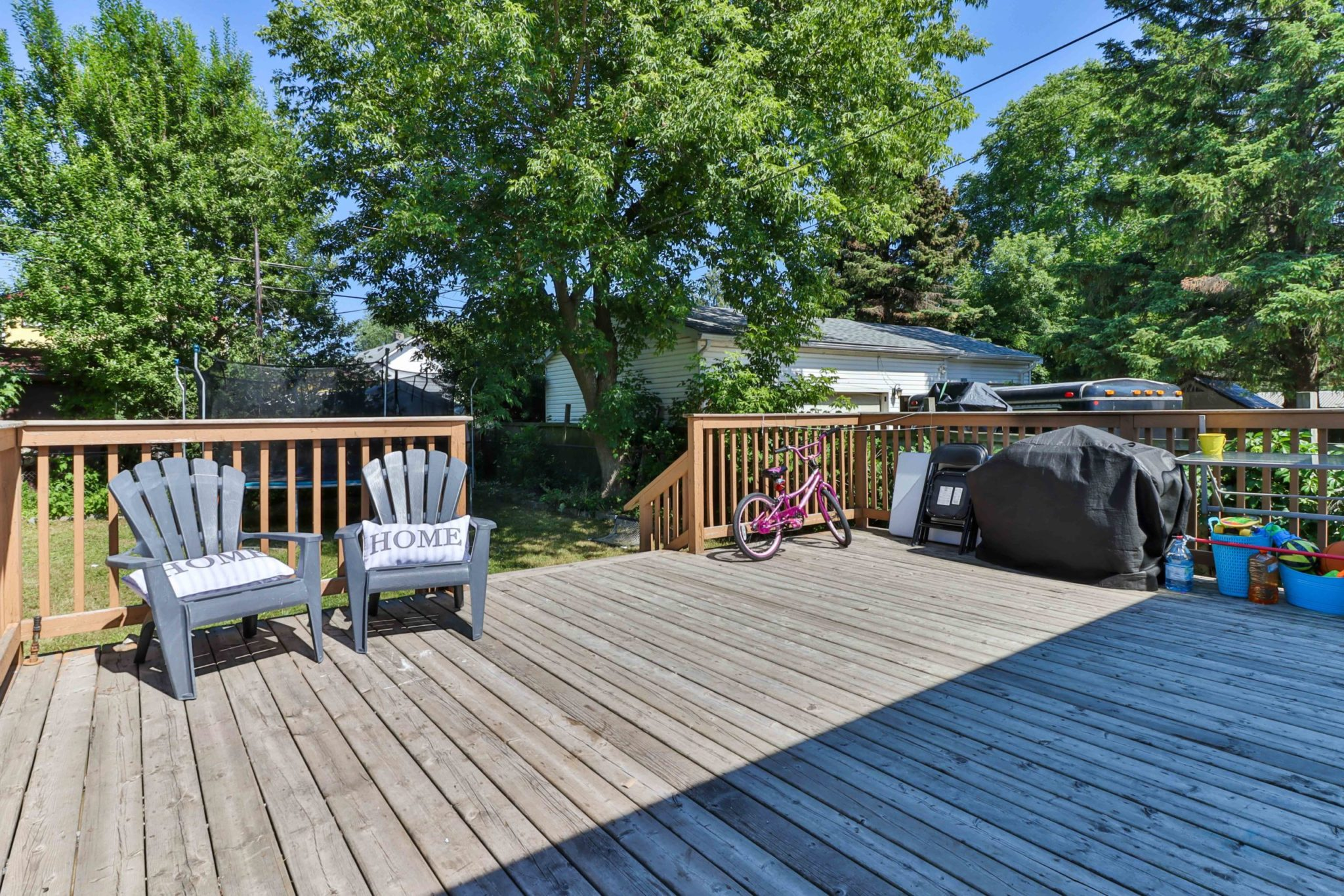 Huge wooden deck with chairs, covered BBQ and bicycle.