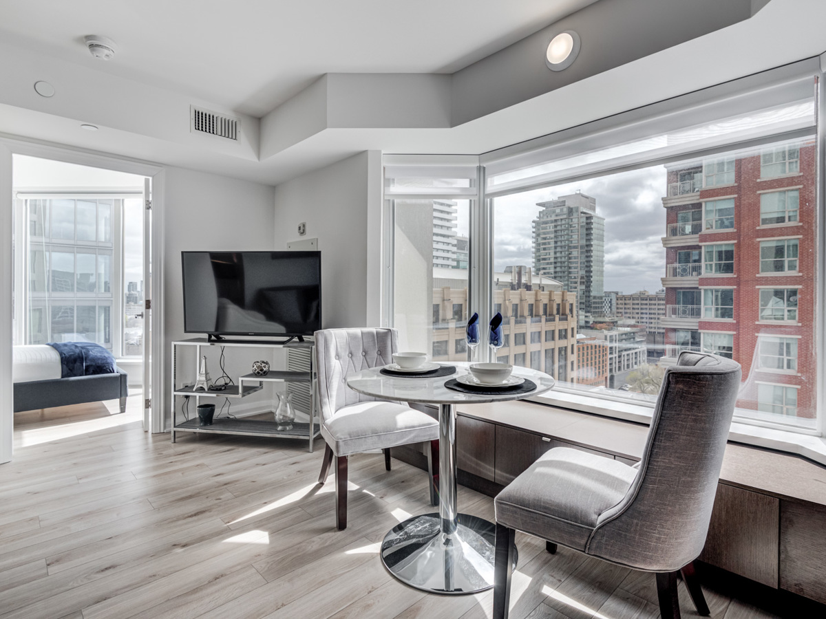 Condo dining room with bay window showing view of Yorkville, Toronto.