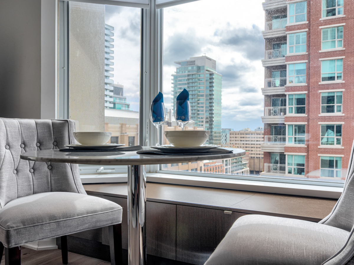 Toronto condo dining room bay window with seating and storage.
