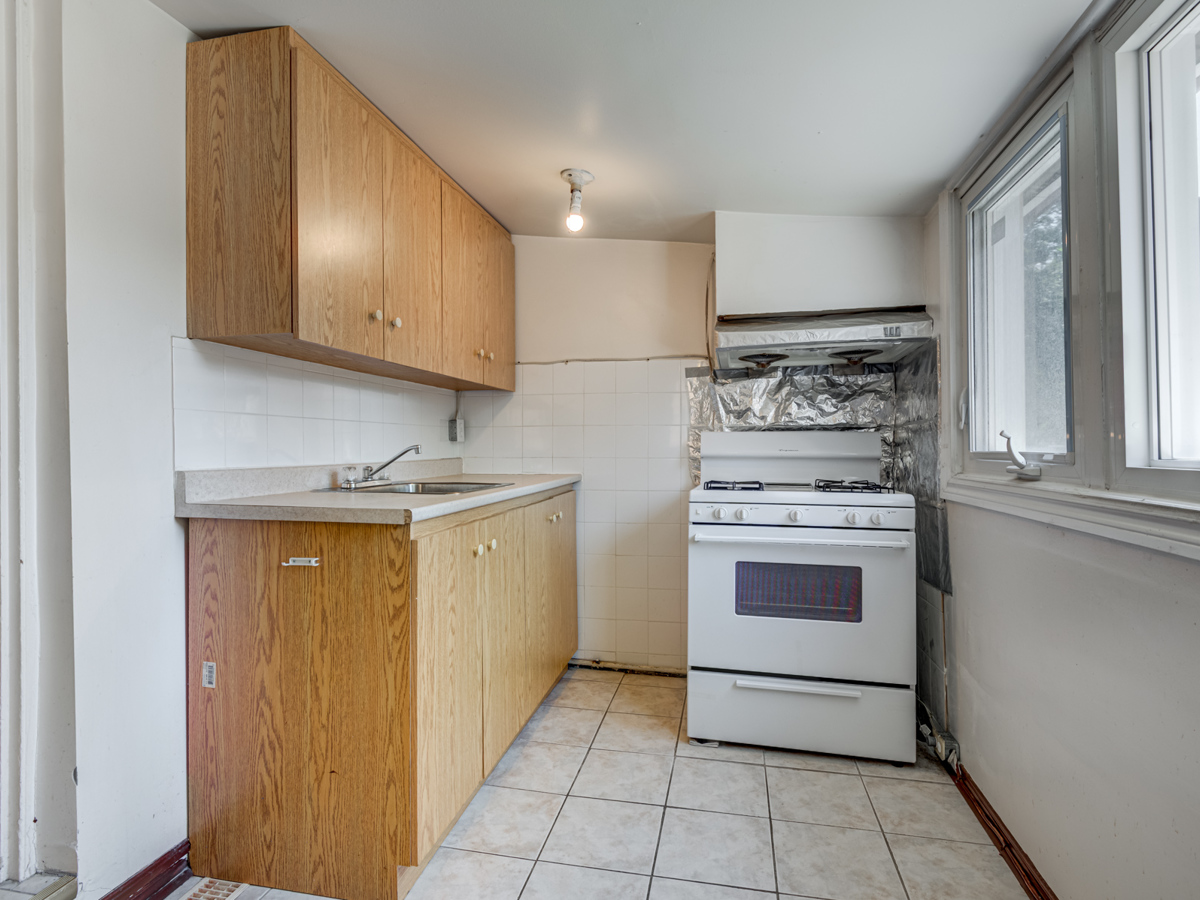 Kitchen with ceramic floors, wall tiles, cabinets and stove.