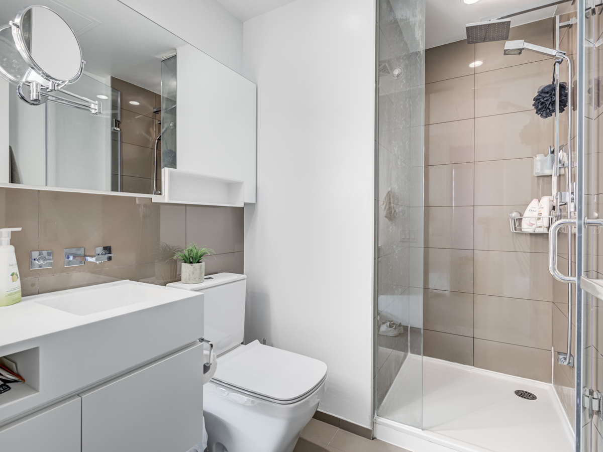 Bathroom with standing shower, Corian counters, large vanity with magnifying mirror, rain-shower, and hand-held faucet.