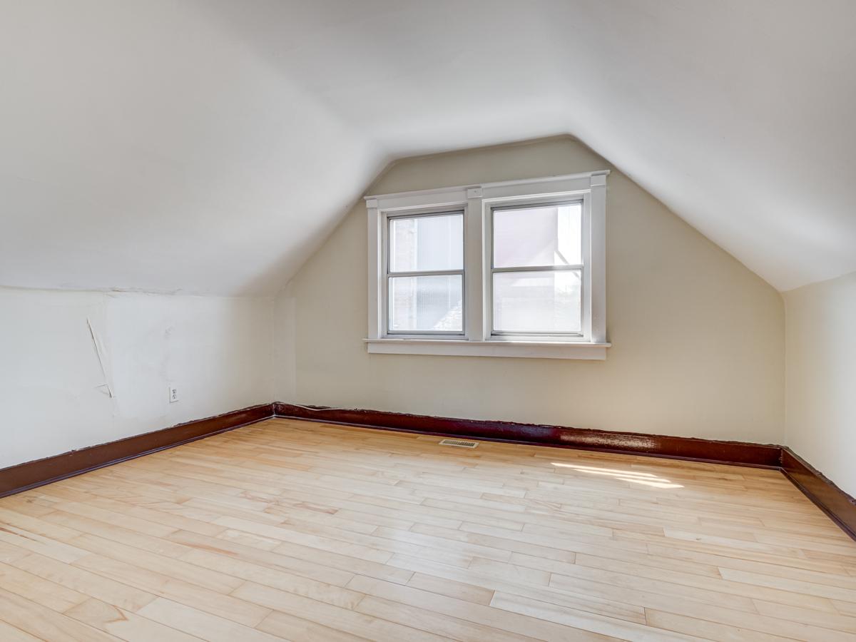 Loft bedroom with hardwood floors and big windows.