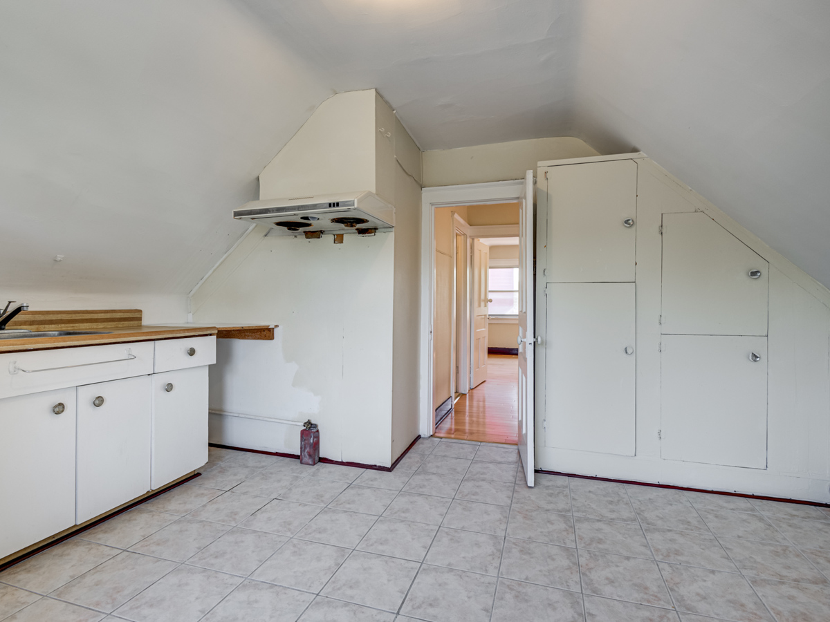 Unfinished loft kitchen with missing appliances.