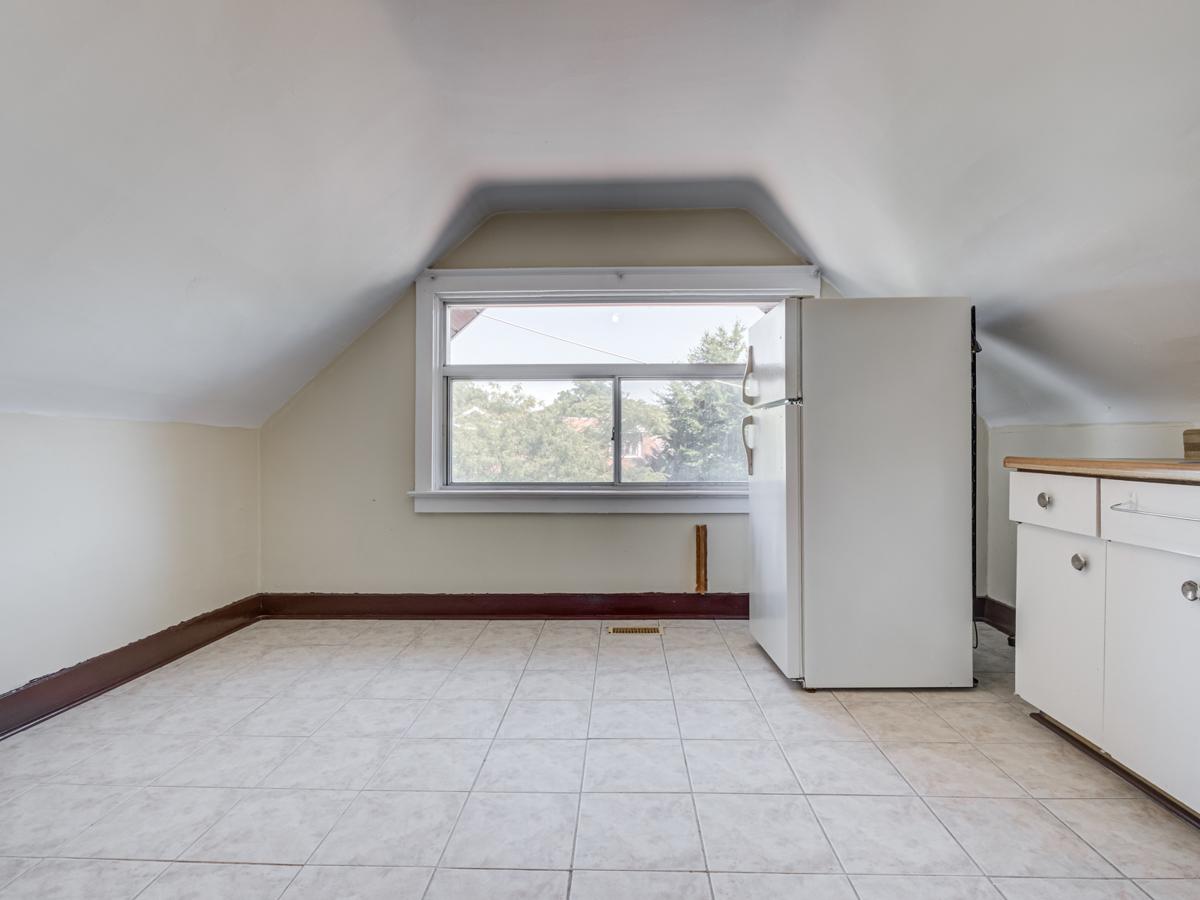 Loft kitchen with large windows and fridge.