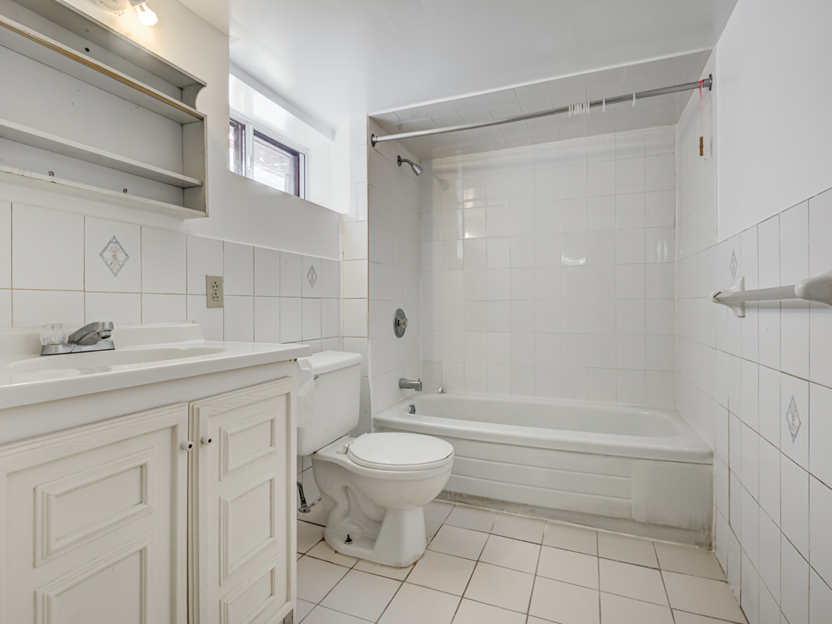 Unfinished 4-piece bath with bathtub, white tiles, sink and several cabinets.