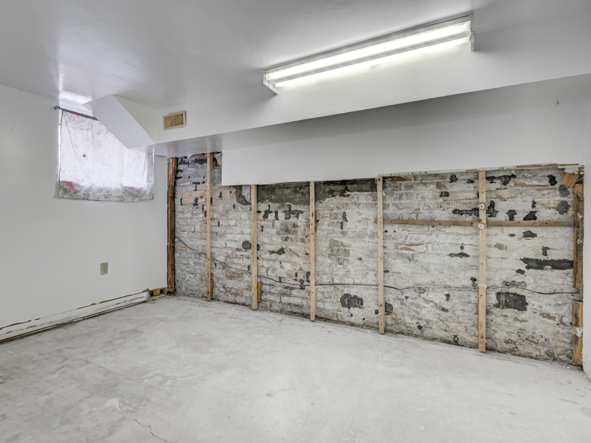 Unfinished basement bedroom with exposed brick wall and fluorescent tube lighting.